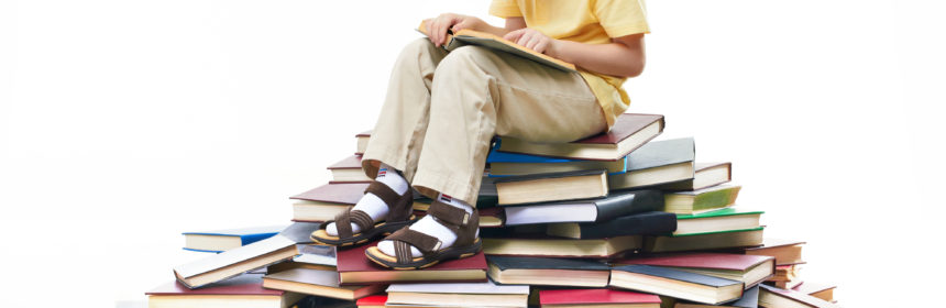 Portrait of diligent pupil sitting on top of books and reading
