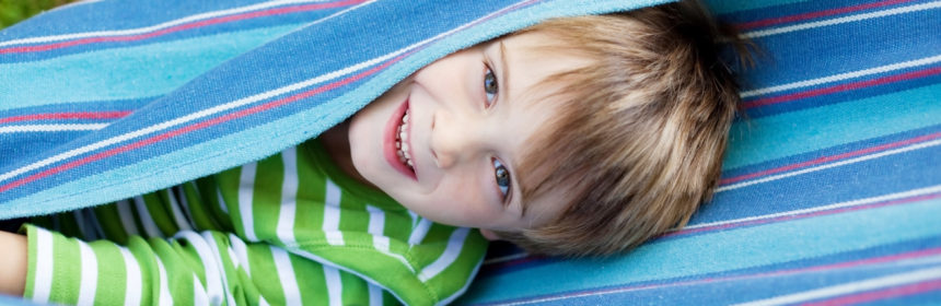 Cheerful child playing and lying inside the hammock